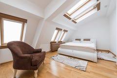 卧室内部在豪华顶楼,顶楼,与屋顶风的公寓 免版税图库摄影
