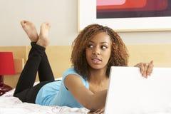 卧室女孩有罪膝上型计算机少年使用 库存照片