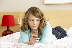 卧室女孩移动电话哀伤少年 免版税库存照片