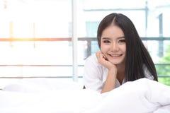 卧室是放松的一个地方 有活动的美丽的妇女在床上 免版税图库摄影