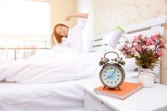 卧室是放松的一个地方 有活动的美丽的妇女在床上 免版税库存图片