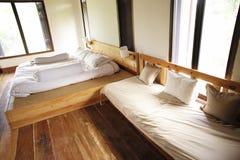 卧室有一张木床和一个木沙发 免版税图库摄影