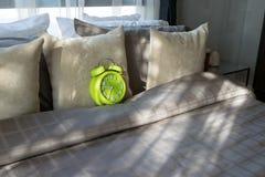 卧室有绿色闹钟的和在床上 免版税库存照片