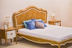 卧室的现代豪华木内部 一间屋子的设计在有床和原始表灯的一家旅馆里 免版税库存照片