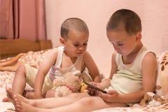 卧室观看的动画片的孩子 在smarfone的儿童游戏 两个兄弟在卧室看智能手机 定调子 免版税图库摄影