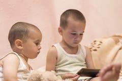 卧室观看的动画片的孩子 在smarfone的儿童游戏 两个兄弟在卧室看智能手机 库存照片