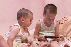 卧室观看的动画片的孩子 在smarfone的儿童游戏 两个兄弟在卧室看智能手机 库存图片