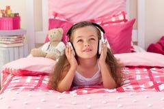 卧室逗人喜爱的女孩听的音乐 图库摄影