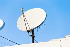 卫星盘和电视天线在房子屋顶有蓝天背景 免版税库存照片