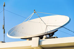 卫星盘和电视天线在房子屋顶有蓝天背景 免版税库存图片
