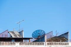 卫星盘和电视天线在老大厦有蓝天背景 图库摄影