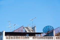 卫星盘和电视天线在老大厦有蓝天背景 免版税图库摄影