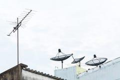卫星盘和电视天线在老大厦有蓝天背景 库存图片