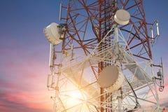 卫星盘在日落的电信塔 免版税库存照片