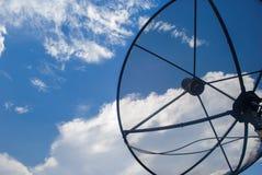 卫星盘天线在与白色云彩的蓝天下 免版税图库摄影