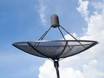 黑卫星盘或电视天线在蓝天多云背景的房子屋顶安装 免版税库存照片