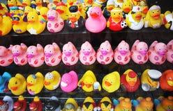 卫生间的许多黄色橡胶鸭子 在显示的销售项目,玩具动物假装与衣裳许多不同  免版税库存图片