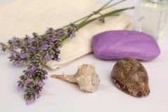 卫生间静物画-一块肥皂和毛巾与海壳和淡紫色 免版税图库摄影