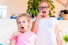 卫生间掠过的牙的两个姐妹 库存照片