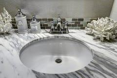 卫生间有白色花岗岩上面的虚荣内阁 水槽和decorat 图库摄影