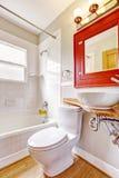 卫生间碗内部毛巾 有镜子的红色内阁和白色船下沉 免版税图库摄影