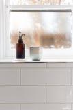 卫生间肥皂分配器和罐在窗口壁架与消极sp 免版税图库摄影