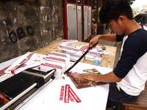 从印刷工司的一名工作者在当广告材料将使用的打印的标志工作为摩托车商店 免版税库存照片