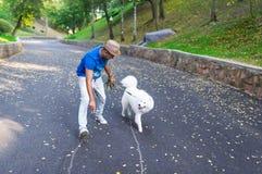 年轻印地安人有休息在有一条白色蓬松狗的公园 库存图片