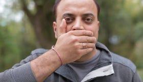 年轻印地安人用他的在他的嘴的手,保持嘴被关闭的表示 免版税库存照片