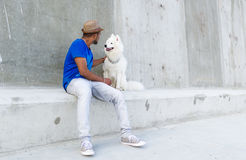 年轻印地安人看一条白色大狗并且保留在狗` s头的一只手 在墙壁上的好空间 免版税库存图片