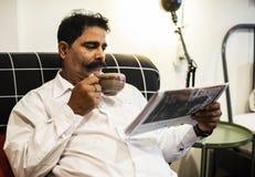 印地安人读书报纸和饮用一个热的饮料 库存图片