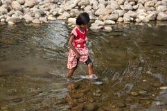印地安农村女孩穿过河 免版税库存图片