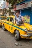 印地安出租汽车司机的画象与他古色古香的老朋友黄色出租汽车的在加尔各答街道上  库存照片
