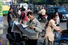 印地安商人读在人群的一张报纸  免版税库存照片