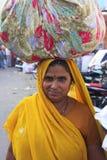 印地安在她的头的妇女运载的捆绑, Bundi,印度 免版税库存图片