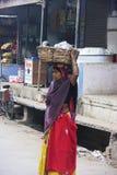 印地安在她的头的妇女运载的篮子, Bundi,印度 免版税库存图片