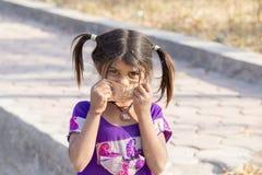 印地安女孩孩子乞求为从游人的金钱在城市街道, Mandu,印度上 免版税库存照片