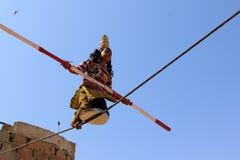 印地安女孩通过走执行街道杂技绳索 免版税库存照片
