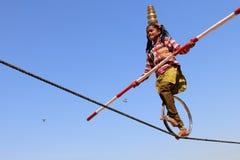 印地安女孩通过走执行街道杂技绳索 免版税库存图片