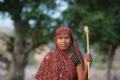 印地安妇女画象用棍子,户外在Ocrhha的乡下,印度 免版税库存照片