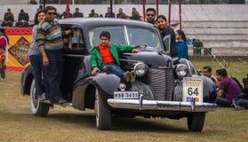 印地安家庭乘坐他们的卡迪拉克葡萄酒汽车,在旗子在政治家葡萄酒汽车集会后 免版税库存照片