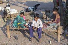 印地安家庭坐有goatling的街道 Mandu,印度 库存图片