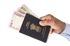 印地安手中护照和的印度卢比 免版税库存照片