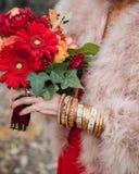 印地安新娘服装用明亮的红色花、金和银手制作了手镯 免版税库存照片