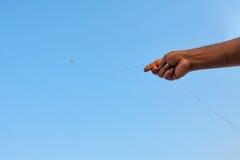 印地安旗子风筝用拿着它的手 库存照片
