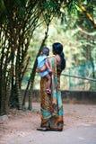 印地安母亲佩带的莎丽服抱绿色公园背景的小孩 免版税库存图片