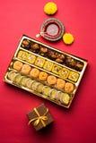 印地安甜点或Mithai diwali节日的与油灯或diya和礼物盒 库存照片
