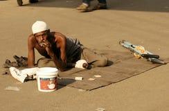 印地安病的在一条繁忙的路的叫化子寻找的帮助 免版税图库摄影