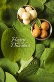印地安节日dussehra,显示有传统印地安甜点pedha的金黄叶子在黄色背景的银色碗,招呼c 免版税库存图片