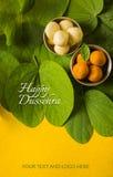 印地安节日dussehra,显示有传统印地安甜点pedha的金黄叶子在黄色背景的银色碗,招呼c 免版税库存照片